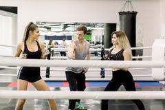 Deux femmes de boxeur se saluer avant combat, leur jeune entra?neur bel se tient entre eux Personnes de boxe photos libres de droits