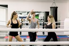 Deux femmes de boxeur se saluer avant combat, leur jeune entra?neur bel se tient entre eux Personnes de boxe photographie stock libre de droits