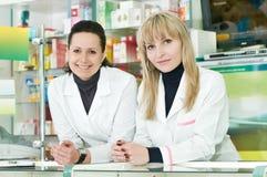 Deux femmes de chimiste de pharmacie dans la pharmacie image stock