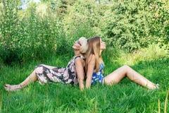 Deux femmes de différentes générations se trouvent sur l'herbe Mère et fille Grand-mère et grand-mère et granddau de petite-fille Photographie stock
