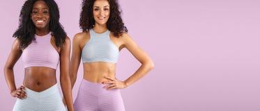 Deux femmes de forme physique dans les vêtements de sport d'isolement au-dessus du fond gris L'espace chopy d'esprit de concept d image stock