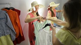 Deux femmes de mode faisant des emplettes choisissant des robes Beaux jeunes clients dans le magasin d'habillement banque de vidéos
