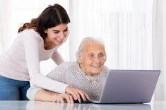 Deux femmes de sourire à l'aide de l'ordinateur portable Photos libres de droits