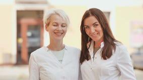 Deux femmes de sourire - blondes dans un manteau blanc Les jeunes spécialistes sont des cosmetologists banque de vidéos