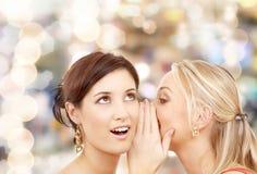 Deux femmes de sourire chuchotant le bavardage Image stock