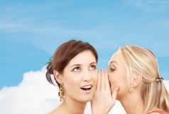 Deux femmes de sourire chuchotant le bavardage Photo stock