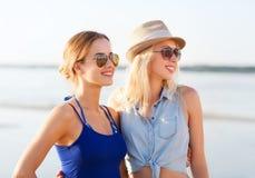 Deux femmes de sourire dans des lunettes de soleil sur la plage Photo stock