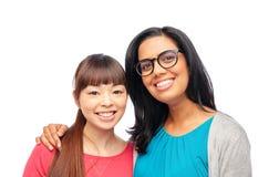 Deux femmes de sourire heureuses ou amis internationaux Image libre de droits