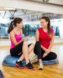Deux femmes de sourire s'asseyant sur les demi boules Photo stock