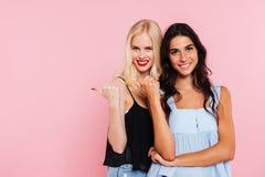 Deux femmes de sourire se dirigeant loin et regardant l'appareil-photo Photographie stock libre de droits