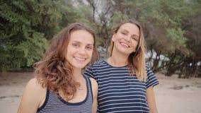 Deux femmes de sourire se tenant au regard de plage directement à la caméra banque de vidéos