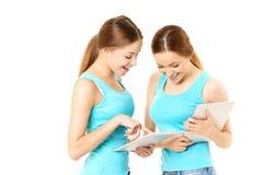 Deux femmes de sourire tenant la tablette Image libre de droits