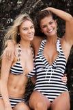 Deux femmes de sourire utilisant les maillots de bain rayés Photos stock