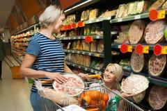 Deux femmes de tous les âges achètent la pizza au supermarché Photographie stock libre de droits
