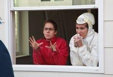 Deux femmes discutent des détails de construction tout en se tenant dans la fenêtre Photographie stock libre de droits