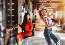 Deux femmes drôles dans un salon de beauté Coiffeur avec le client Brune sexy et fille blonde images libres de droits
