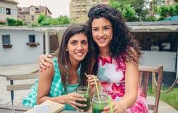 Deux femmes embrassées avec des smoothies regardant l'appareil-photo Images stock
