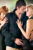 Deux femmes embrassant avec le jeune homme, à l'extérieur Images stock