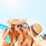 Deux femmes embrassant l'ami sur la plage Images stock