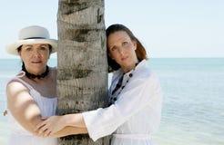Deux femmes embrassant l'arbre Photographie stock
