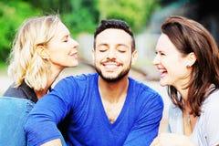Deux femmes embrassant l'homme bel sur ses joues images stock