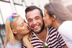 Deux femmes embrassant un homme Photos stock