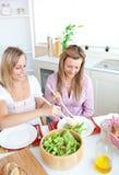 Deux femmes en bonne santé mangeant de la salade dans la cuisine Photographie stock