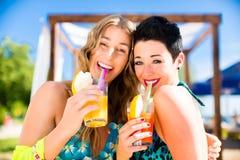 Deux femmes en cocktails potables de barre de plage Photographie stock