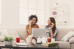 Deux femmes en ligne avec la carte de crédit et l'ordinateur portable Images stock