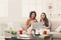 Deux femmes en ligne avec la carte de crédit et l'ordinateur portable Photos stock
