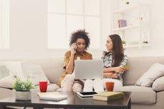 Deux femmes en ligne avec la carte de crédit et l'ordinateur portable Photos libres de droits