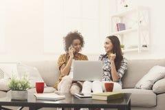 Deux femmes en ligne avec la carte de crédit et l'ordinateur portable Image stock