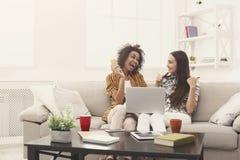 Deux femmes en ligne avec la carte de crédit et l'ordinateur portable Photographie stock libre de droits