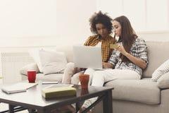 Deux femmes en ligne avec la carte de crédit et l'ordinateur portable Photographie stock