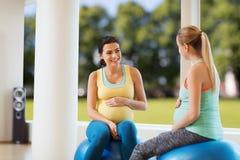 Deux femmes enceintes heureuses s'asseyant sur des boules dans le gymnase Photos stock