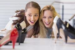 Deux femmes enthousiastes regardant des chaussures de talon Photo libre de droits