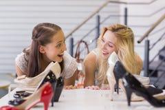 Deux femmes enthousiastes regardant des chaussures de talon Photographie stock