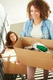 Deux femmes entrant dans la nouvelle boîte de transport à la maison en haut Photographie stock libre de droits