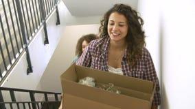 Deux femmes entrant dans la nouvelle boîte de transport à la maison en haut clips vidéos