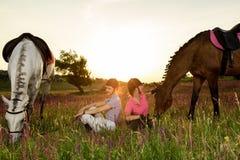 Deux femmes et deux chevaux extérieurs en nature heureuse de coucher du soleil d'été ensemble Photos stock