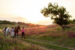 Deux femmes et deux chevaux extérieurs en nature heureuse de coucher du soleil d'été ensemble Image libre de droits