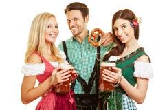 Deux femmes et homme avec de la bière à Photographie stock