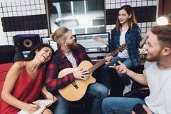 Deux femmes et deux hommes chantent une chanson dans une guitare dans un studio d'enregistrement moderne photos stock