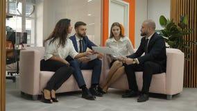Deux femmes et deux hommes s'asseyent sur le devanchiki dans le bureau et un des hommes explique l'essence des documents clips vidéos