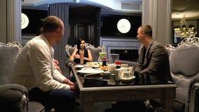 Deux femmes et deux hommes se reposant dans des fauteuils confortables se reposent dans un restaurant pour des cocktails sushi, t banque de vidéos