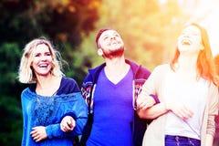 Deux femmes et jeune homme marchant et appréciant le soleil photographie stock