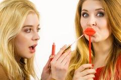 Deux femmes et produits de lèvre Photographie stock
