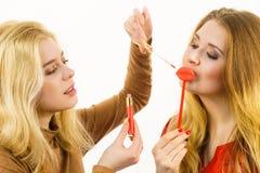 Deux femmes et produits de lèvre Images stock