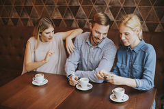 Deux femmes et un homme au café, parlant, riant et appréciant le thei Photos libres de droits