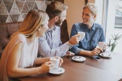 Deux femmes et un homme au café, parlant, riant et appréciant le thei Image libre de droits